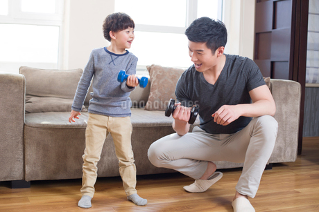 Young father and son exercising at homeの写真素材 [FYI02224345]
