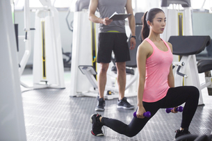 Young woman working with trainer at gymの写真素材 [FYI02224409]