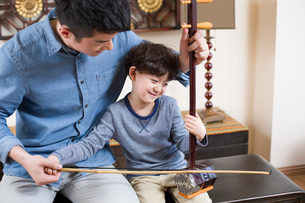 Father teaching traditional musical instrument erhuの写真素材 [FYI02224444]