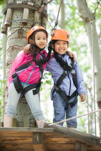 Little girls playing in tree top adventure parkの写真素材 [FYI02224552]