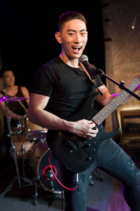 Young man singing with guitar on stageの写真素材 [FYI02224602]