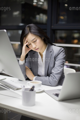 Businesswoman working late in officeの写真素材 [FYI02224608]
