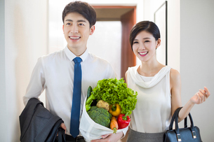 Young couple arriving home with fresh vegetablesの写真素材 [FYI02224646]