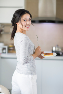 Young woman eating breakfast at homeの写真素材 [FYI02224705]