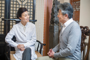 Female Chinese doctor talking with patientの写真素材 [FYI02224735]
