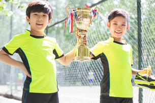Happy children in sportswear showing their trophyの写真素材 [FYI02224749]