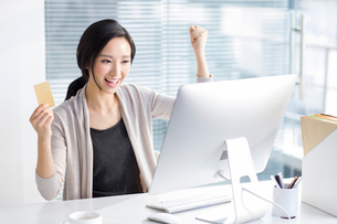 Young woman shopping online in officeの写真素材 [FYI02224754]