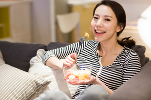 Happy young woman eating fruit salad on sofaの写真素材 [FYI02224786]