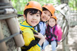 Happy children playing in tree top adventure parkの写真素材 [FYI02224820]