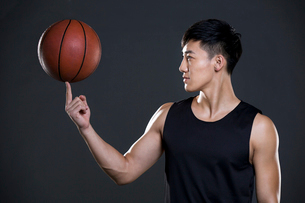 Young man spinning basketball on fingerの写真素材 [FYI02224849]