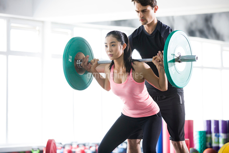 Young woman working with trainer at gymの写真素材 [FYI02224863]