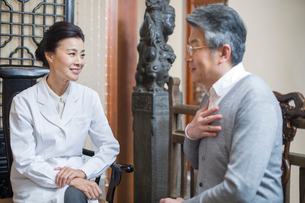 Female Chinese doctor talking with patientの写真素材 [FYI02224900]
