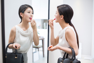 Young woman looking into a mirror applying lipstickの写真素材 [FYI02224953]