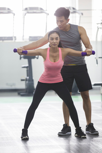 Young woman working with trainer at gymの写真素材 [FYI02224968]