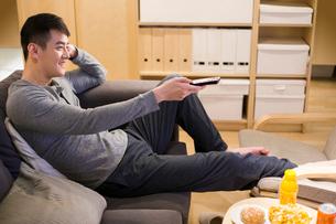 Young man watching TV on living room sofaの写真素材 [FYI02225063]