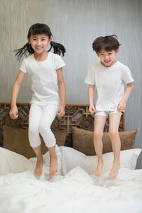 Little children jumping on bedの写真素材 [FYI02225107]