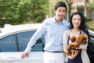Young couple leaning on car with their pet dogの写真素材 [FYI02225108]
