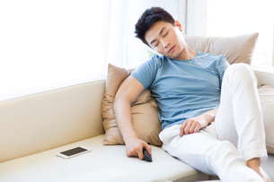 Young man sleeping on the sofaの写真素材 [FYI02225134]