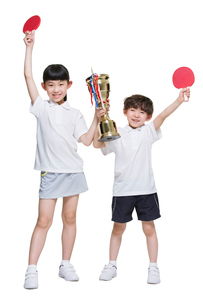 Cute children holding table tennis rackets and trophyの写真素材 [FYI02225136]