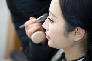 Makeup artist applying make-up to young womanの写真素材 [FYI02225155]