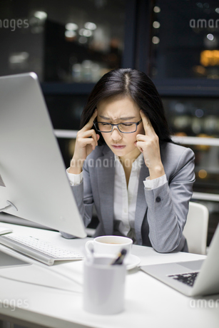 Businesswoman working late in officeの写真素材 [FYI02225172]