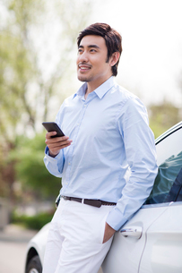 Young man leaning on car with smart phoneの写真素材 [FYI02225179]