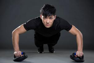 Young man doing push-upsの写真素材 [FYI02225192]