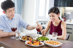 Romantic young couple dining at homeの写真素材 [FYI02225222]