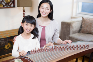 Mother teaching traditional musical instrument zitherの写真素材 [FYI02225227]