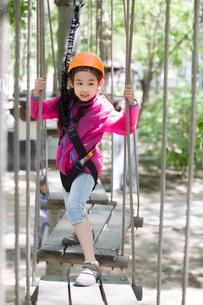 Little girl playing in tree top adventure parkの写真素材 [FYI02225237]