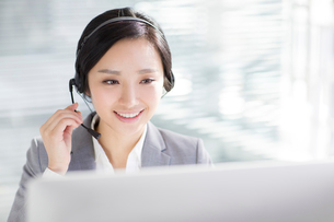 Businesswoman working in office with headsetの写真素材 [FYI02225249]