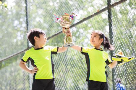 Happy children in sportswear showing their trophyの写真素材 [FYI02225257]
