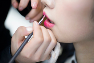 Makeup artist applying make-up to young womanの写真素材 [FYI02225261]