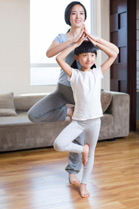 Young mother and daughter doing yoga at homeの写真素材 [FYI02225282]
