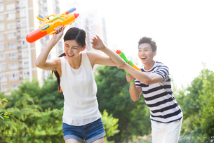 Happy young couple playing squirt gunsの写真素材 [FYI02225301]
