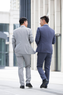 Confident businessmen talking and walking outdoorsの写真素材 [FYI02225303]