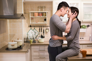 Young couple embracing in kitchenの写真素材 [FYI02225306]