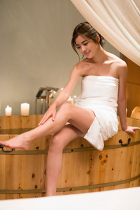 Beautiful young woman sitting by the bathtubの写真素材 [FYI02225307]