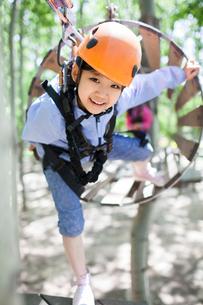 Little girl playing in tree top adventure parkの写真素材 [FYI02225308]