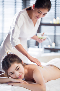 Young woman receiving back massage at spa centerの写真素材 [FYI02225324]