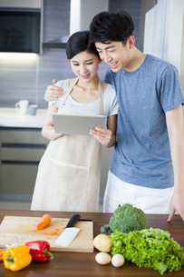 Happy young couple using digital tablet in kitchenの写真素材 [FYI02225332]