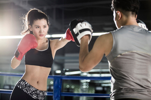 Female boxer training with coachの写真素材 [FYI02225368]