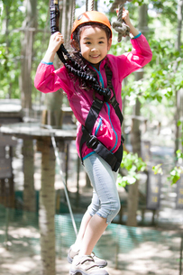 Little girl playing in tree top adventure parkの写真素材 [FYI02225402]
