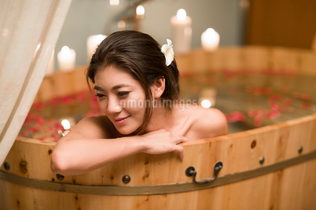 Beautiful young woman in bathtub with rose petalsの写真素材 [FYI02225428]