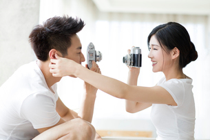 Young couple taking photos at homeの写真素材 [FYI02225430]