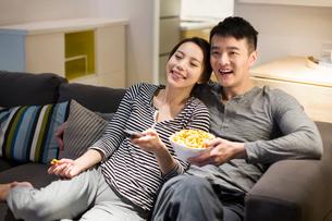 Young couple watching TV on living room sofaの写真素材 [FYI02225472]