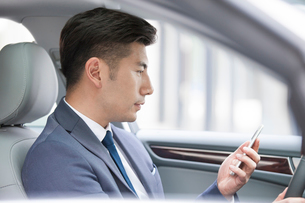 Confident businessman holding smart phone in a carの写真素材 [FYI02225506]