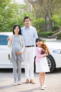 Young family getting out of car with their pet dogの写真素材 [FYI02225539]