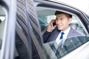Confident businessman talking on cell phone inside carの写真素材 [FYI02225551]