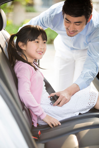 Father fastening seat belt for daughterの写真素材 [FYI02225554]
